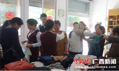 志愿者帮助受助者挑选衣物。
