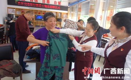 受助者向志愿者展示自己选中的衣物。