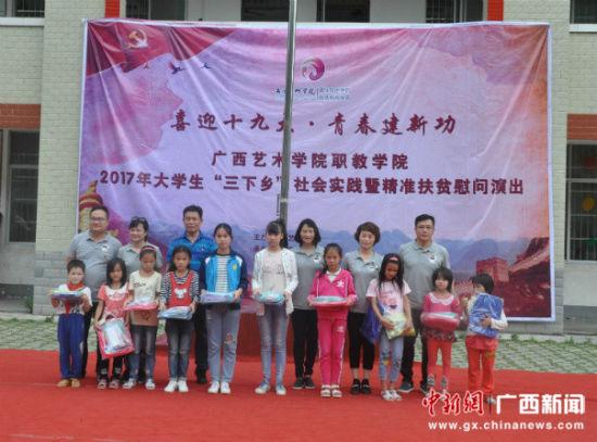 图为师生们向贫困小学生赠送文具。