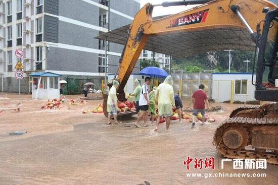 图为男教职工堆积沙袋堵住极端水域。张文源 摄