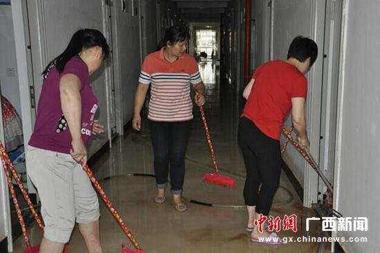 图为后勤阿姨清扫6号公寓一楼积水处。张文源 摄