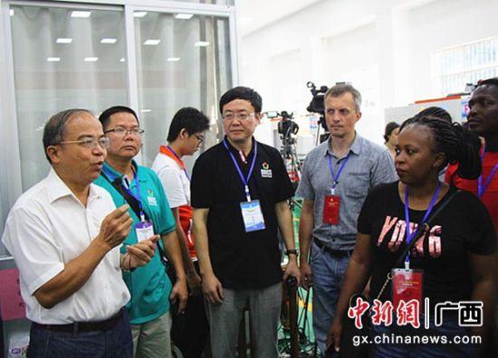 广西机电职业技术学院党委书记冯国忠(左一)向国际观摩团介绍大赛情况。高瞻 摄