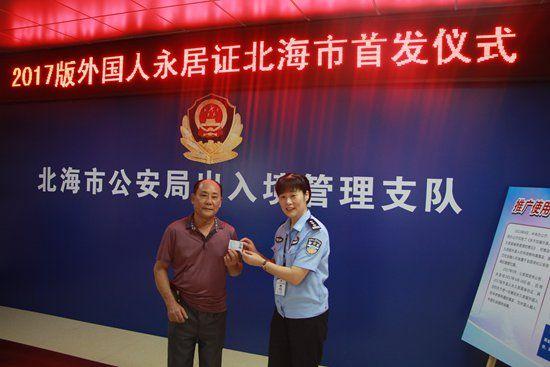 图为杨慧军向前来代替其母亲领取证件的蔡先生颁发了外国人永居证。