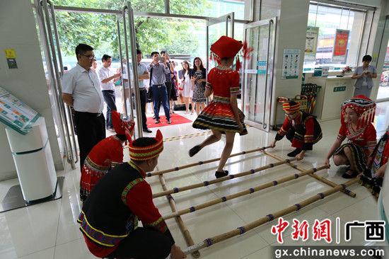 农行南宁国贸支行跳竹竿舞迎客客欢心。