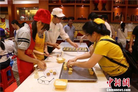 图为糕点师傅在教学生制作月饼 林馨 摄