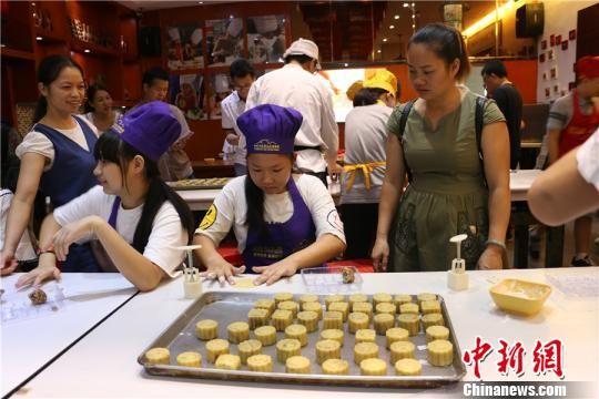 图为学生在动手制作月饼 林馨 摄
