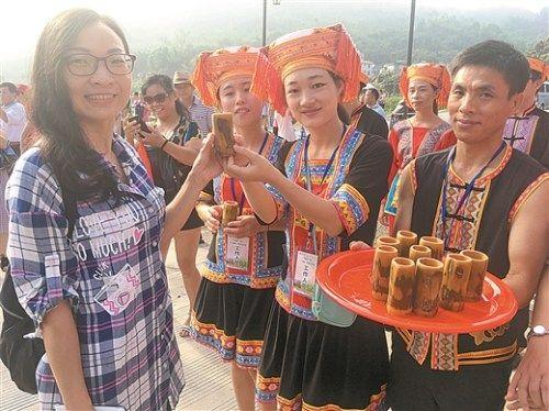 在夏宜瑶族乡,游客们刚进寨门就尝到香醇的米酒。 本报记者 梁乾胜/摄
