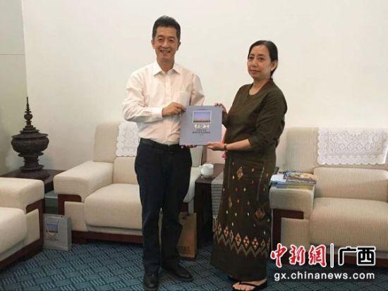 图为广西国际文化交流中心向缅甸驻南宁总领馆赠送印象梵花缅甸风情风光摄影集。杨陈 摄