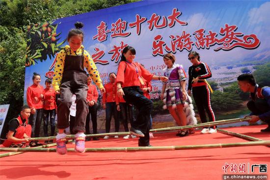 游客在体验竹竿舞。覃庆和 摄