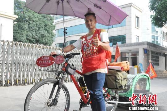 图为冯波和他改装过的带车斗的自行车。 钟建珊 摄