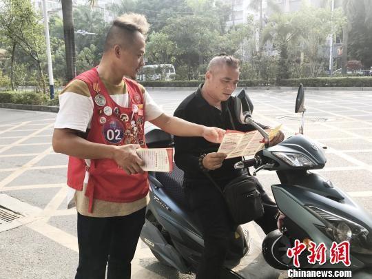 图为冯波向路过行人发放无偿献血宣传传单。 钟建珊 摄