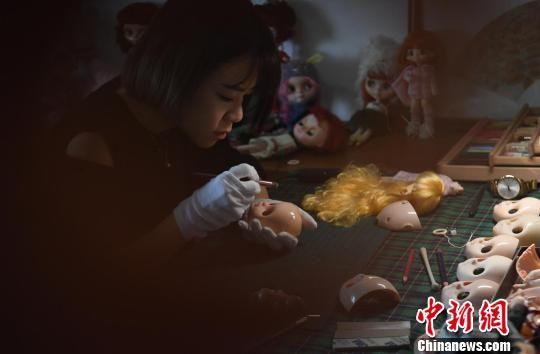 图为黄思林在工作室内替娃娃改妆。 俞靖 摄