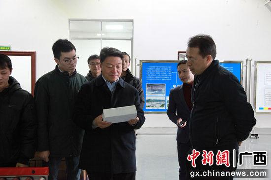 图二为 邱明宏(右)向韩宝昌(中)介绍跨境电商产品分类。