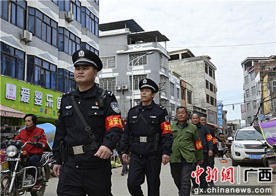 图为左启亮带领社区义务巡逻队走街串巷巡逻。甘勇 摄