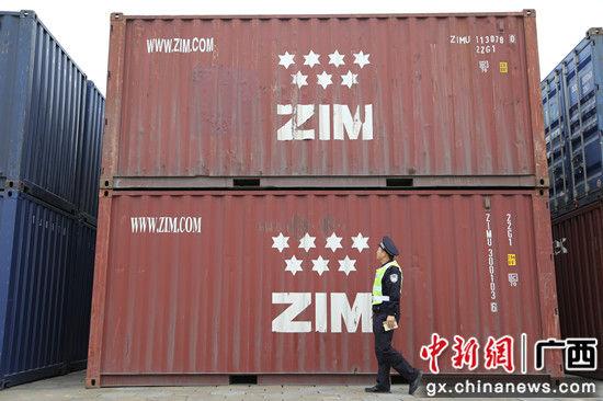 10.图为1月30日,黄鸿宇在一处外来集装箱下走过。 梁荫发 摄