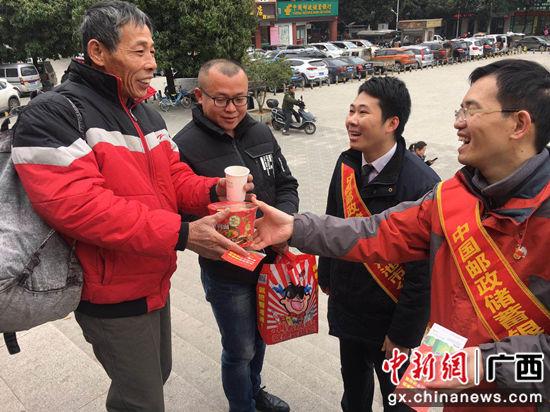 邮储银行河池市分行志愿者亲手将食物送到返乡群众的手上。