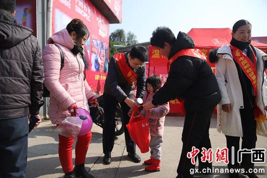 邮储银行梧州市分行黄杰文副行长亲手将八宝粥送到返乡小女孩的手上。