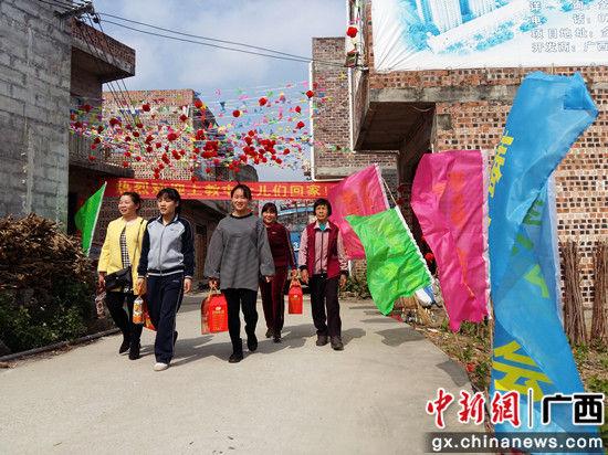 村里挂起横幅和彩旗欢迎女儿们回娘家。