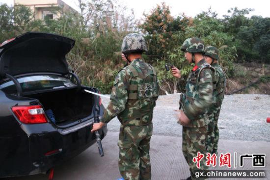 边防官兵在车尾箱查货一把大砍刀。
