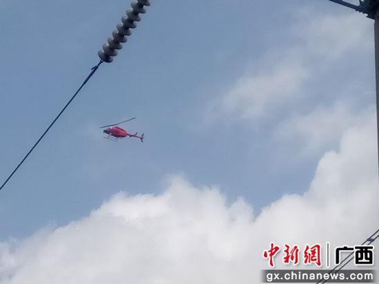 图为直升机高压输电巡线。