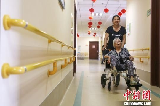 图为一名家属陪伴在孝慈苑内养老的老人。 徐冰 摄
