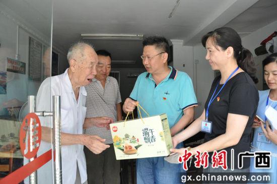 志愿者给老人送粽子。
