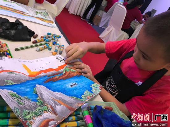 来自马来西亚当地的小朋友正在作画。