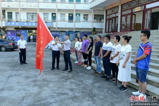 学院领导为师生代表三下乡出行授旗。朱名明 摄