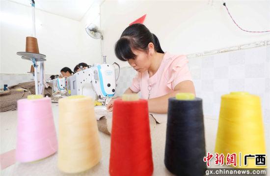 一名女工在广西柳州市融安县扶贫小微工厂车间里生产童装。谭凯兴 摄