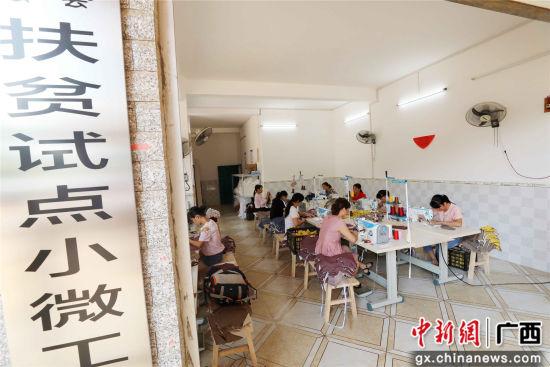 女工在广西柳州市融安县扶贫小微工厂车间里生产童装。谭凯兴 摄