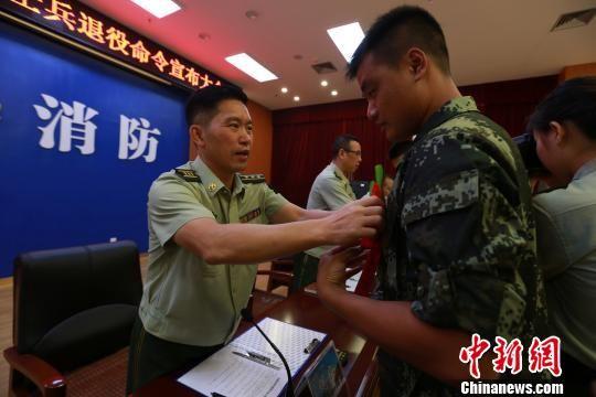 9月20日,武警广西消防总队桂林支队政委为退伍老兵卸下警衔带上红花。 熊有发 摄