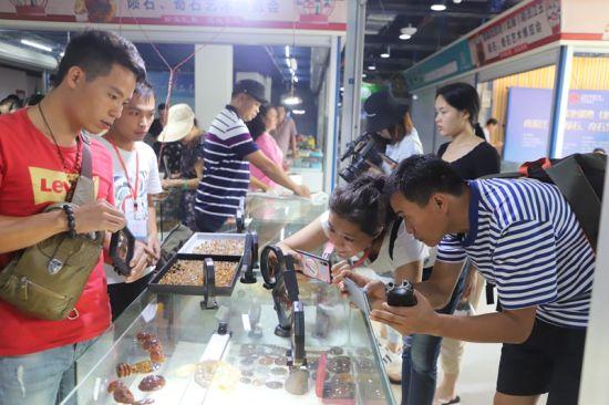图为南流江玉石吸引游客驻足拍摄。
