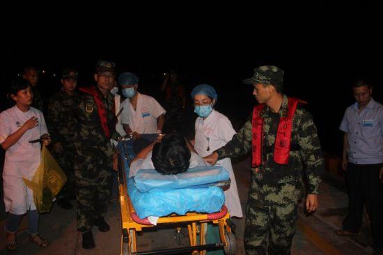 图为海警官兵帮运送患者。