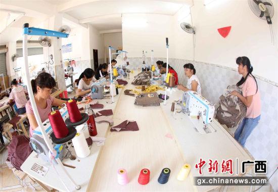 8月17日,女工在广西柳州市融安县扶贫小微工厂车间里生产童装。(谭凯兴 摄)