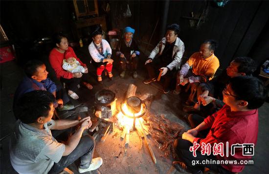 81岁的老党员贾祖咪(左五)组织该村部分贫困户户主在火塘旁听红水乡党委书记韦建新(左六)宣传讲解国家产业扶贫政策。石峰摄