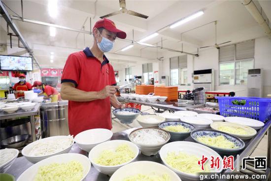 广西融安县泗顶镇三坡村贫困户覃福晏在广东东莞市某电子生产企业食堂务工。谭凯兴 摄