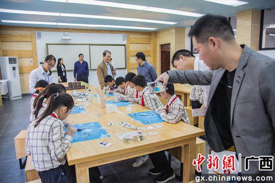 领导嘉宾在新建的南宁市五象新区第一实验小学参观学生的文化展示 。 陈冠言 摄