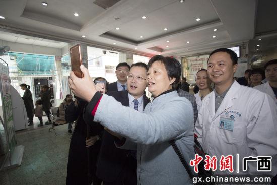 柳州市工人医院院长李兵(左)在指导一女士扫码关注工人医院智慧医院。