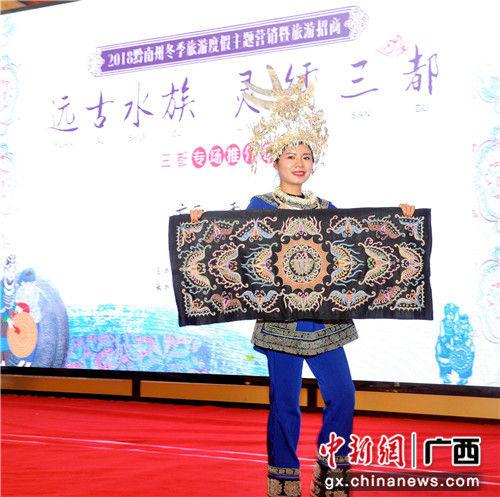 图为推介会上,一名工作人员展示黔南的特色织绣。