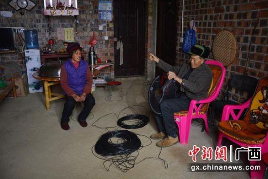 图为在家中编织产品的苏冠球(右)。