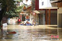 广西融水县半个城被洪水浸泡 居民乘船出行