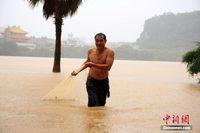 雨水冲击广西河流水位持续上涨 民众雨中网鱼