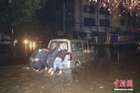冬日暴雨致广西柳州街道内涝 车辆如在河中开行
